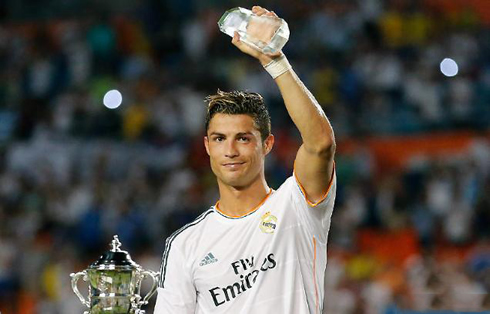 Cristiano Ronaldo holding the MVP trophy and the Guinness International Champions Cup on his hands, in 2013