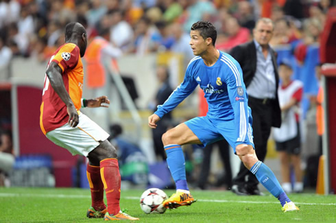 Cristiano Ronaldo prepares to dribble a Galatasaray defender, with Fatih Terim looking at him in second plan