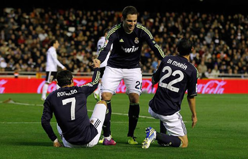 Gonzalo Higuaín stretching his hands to Cristiano Ronaldo and Angel di María, in a Real Madrid match in 2013