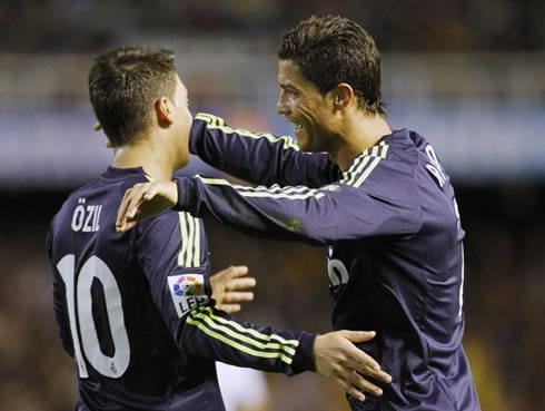 Cristiano Ronaldo about to hug Mesut Ozil, in a Real Madrid game in 2013