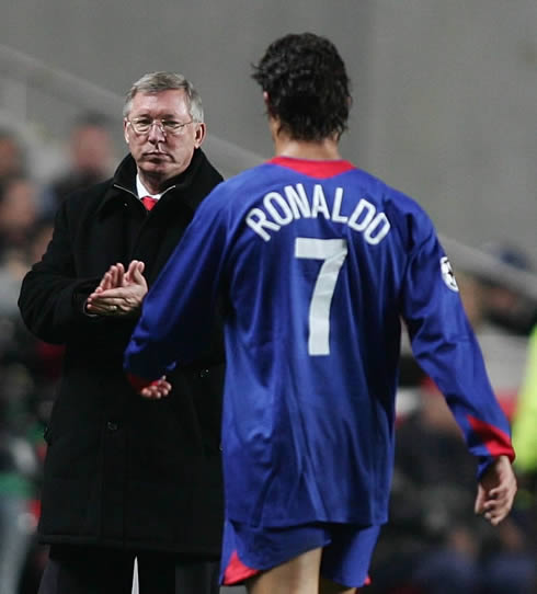 Cristiano Ronaldo in a blue Manchester United jersey, walking towards Sir Alex Ferguson