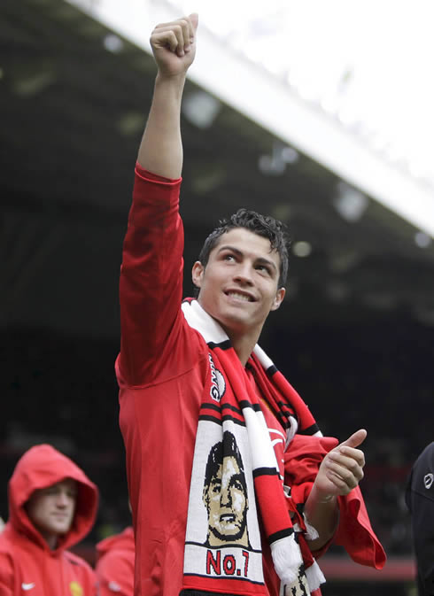 Cristiano Ronaldo celebrating a Manchester United trophy at Old Trafford, with Wayne Rooney behind him