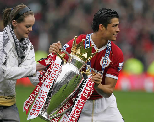 Cristiano Ronaldo holding the English Premier League trophy at Old Trafford, with a pretty chick near him