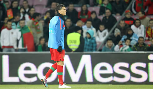 Cristiano Ronaldo during the warm-up for Portugal, with a Leo Messi banner/ad campaign on his the board behind him