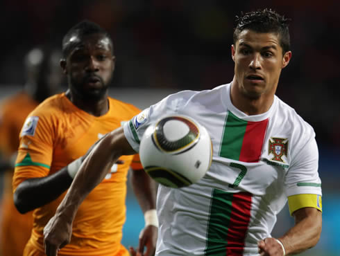 Cristiano Ronaldo in a white Portugal jersey, running very focused after the ball
