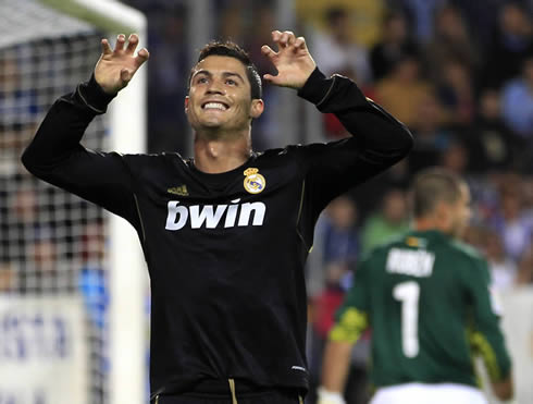 Cristiano Ronaldo in a Real Madrid black jersey, celebrating a goal with his fingers