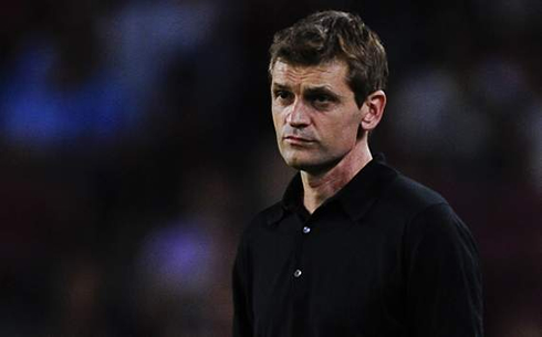 Tito Vilanova wearing a black shirt and suit, in a Barcelona match in 2012-2013